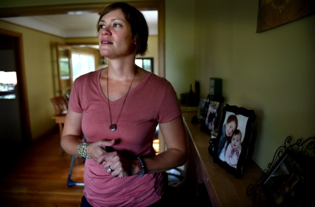 """When we (she and her husband) see that memorial it brings back a feeling of being grateful for the days we have here,"" said Sarah Mundy-Evans in her Robbinsdale home on Wednesday, July 26, 2017. She was driving her car across the Interstate 35W bridge when it collapsed on Aug. 1, 2007, but walked away with minor injuries. Ten years later she has married her fiancee and has two children, Oliver, 5, and Marlow, 1, pictured at right in her living room. (Jean Pieri / Pioneer Press)"