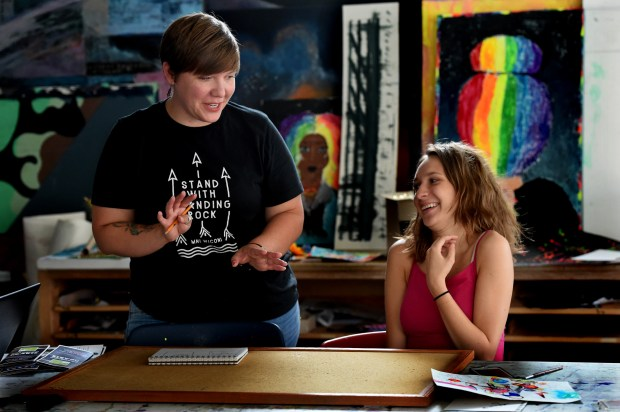 Lindsay Walz, left, talks with her intern, Maeve Bartell, about designing a bulletin board to promote the youth advisory board at courageous heARTs, a non-profit art center in Minneapolis for troubled youth, on Wednesday, July 26, 2017. Walz, now 34, escaped after being trapped underwater in her car when it fell into the Mississippi River during the Interstate 35W bridge collapse on Aug. 1, 2007. Bartell, 18, is majoring in art at Minneapolis Community and Technical College. (Jean Pieri / Pioneer Press)
