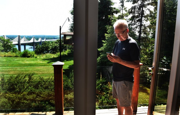 Dave Robson, a commercial real estate agent, checks his cellphone on his deck Wednesday, July 5, 2017. He owns the first house to the north of the new St. Croix Bridge on the Wisconsin side. (Jean Pieri / Pioneer Press)