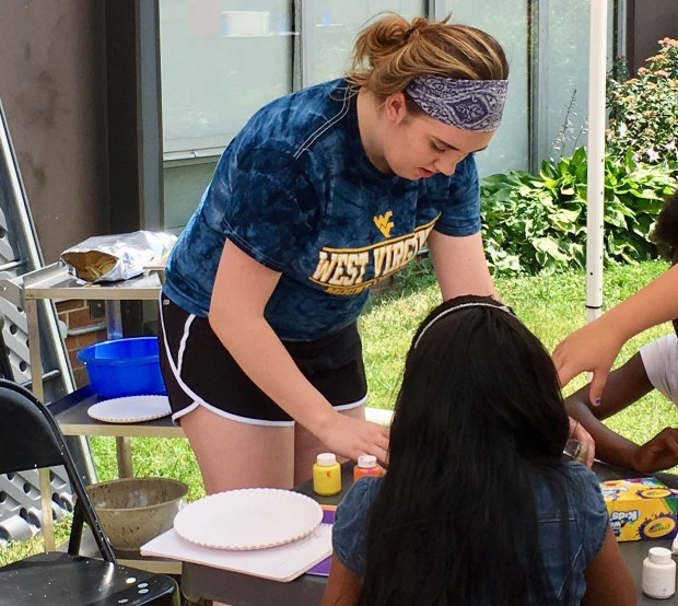 Natalie Grams, 16, helps a young girl with a craft. Grams was one of about 60 youth volunteers who came to St. Paul this week to serve the community through Youthworks. (S. M. Chavey / Pioneer Press)