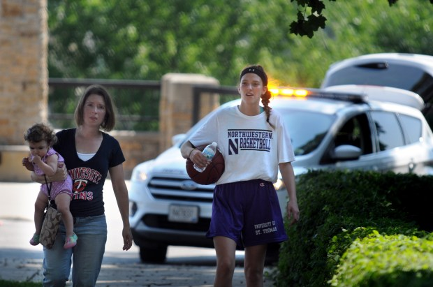 Liz Peterson, holding her 14-month-old daughter Lucy, walks with Minnehaha Academy student Taytum Rhoades away from the scene of an explosion Wednesday, Aug. 2, 2017. Taytum, a resident of St. Paul's Mac Groveland neighborhood, was inside the gymnasium when the explosion happened. (Dave Orrick / Pioneer Press)