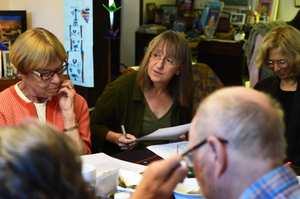 "Su Smallen, center, receives feedback from Deborah Keenan and other students on the draft of her poem ""House Finch,"" during a poetry class in Keenan's St. Paul home, Monday, June 26, 2017. One student suggests renaming the poem ""The Ability to Wait."" (Scott Takushi / Pioneer Press)"