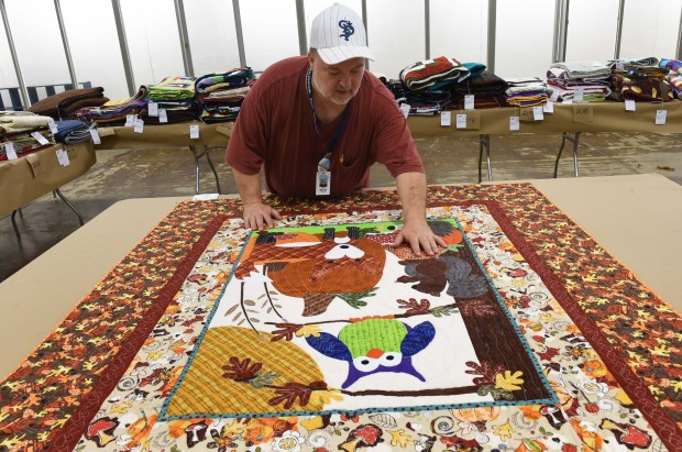 "David Shattuck judges the quilts in the Creative Activities Building at the Minnesota State Fair, August 15, 2017. He estimated there were more than 300 quilt entries -- so many that he needed a ""scribe"" to take down his scoring. (Scott Takushi / Pioneer Press)"