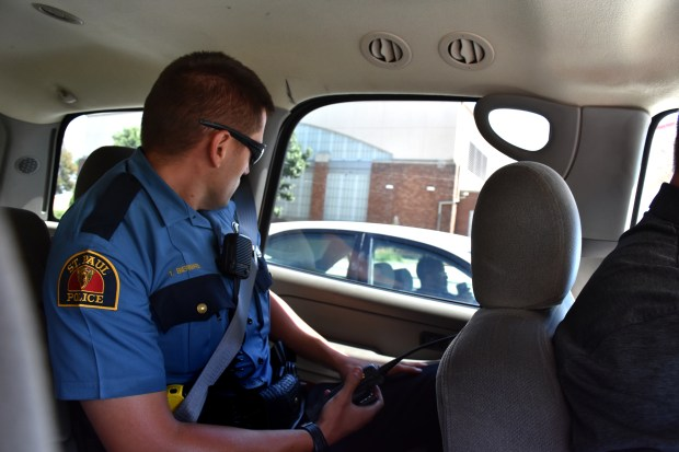 St. Paul Officer Tim Biermaier looks over at a man who is holding his cell phone while behind the wheel on Snelling Avenue on Wednesday, Aug. 23, 2017. It's part of a St. Paul police distracted driving campaign in conjunction with Minnesota State Fair traffic. Police later cited the man for texting and driving. (Mara H. Gottfried / Pioneer Press)