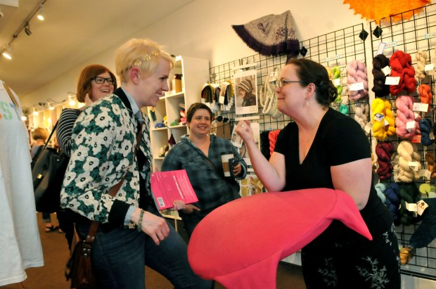 Local author and craftivist, Lara Neel, right, shares how she created a pussy pet bed with Amber Lenhoff, left, Laura Winterstein, center, and Sarah Olson, right at Knit and Bolt in NE Minneapolis where she was signing copies of her new book, 'Crafting the Resistance', on Friday, August 25, 2017. Neel has helped spawn a movement of craftivism or the making of crafts that protest something. (Ginger Pinson / Pioneer Press)