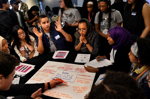 Woodbury High School senior Kamal Suleiman raises his hands while discussing diversity with other students at a round table in Falcon Heights in February 2017. Others pictured include, from left, Isra Hassan (hands folded) from Anoka High School and Nawn Maxamed (purple scarf) from Burnsville High School, while Andy Baran from Orono High School writes down their ideas. (Jean Pieri / Pioneer Press)