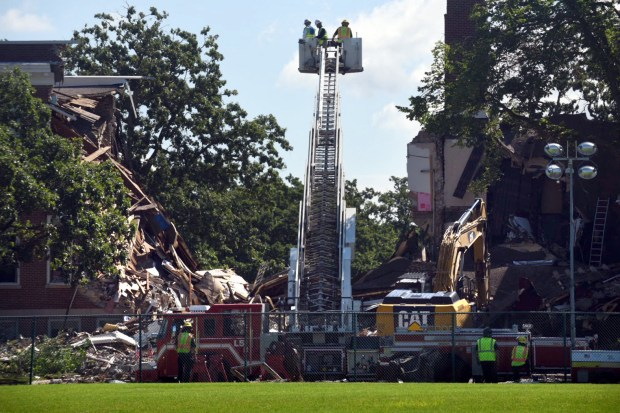 Roger Evans, left, a senior investigator with the National Transportation Safety Board, and NTSB Board Member Christopher Hart, right, survey the wreckage with a Minneapolis firefighter from the ladder of a fire truck at Minnehaha Academy Friday, Aug. 4, 2017. The NTSB is leading the investigation into a natural gas explosion that leveled a building and killed two Wednesday at the Minneapolis private school. (Dave Orrick / Pioneer Press)
