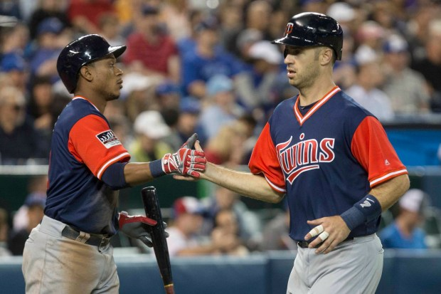 Minnesota Twins' Jorge Polanco, left, congratulates Joe Mauer, who scored on an Eduardo Escobar sacrifice fly against the Toronto Blue Jays during the fifth inning of a baseball game Friday, Aug. 25, 2017, in Toronto. (Chris Young/The Canadian Press via AP)
