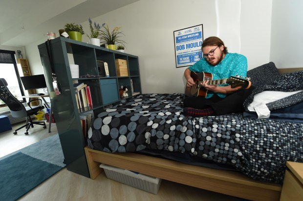 Kyle Werstein, a 25-year-old software developer and musician, practices his music in his apartment at The Ray, a new apartment building in St. Paul's Midway area, on Wednesday, Sept. 6, 2017. Werstein has lived in the 455-square foot apartment since the end of July. (Scott Takushi / Pioneer Press)