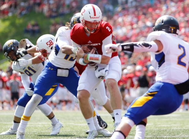 Saint John's sophomore quarterback Jackson Erdmann is swarmed by St. Scholastica players in the Johnnies' 98-0 victory last Saturday in Collegeville, Minn. (St. John's University/Alexus Jungles)