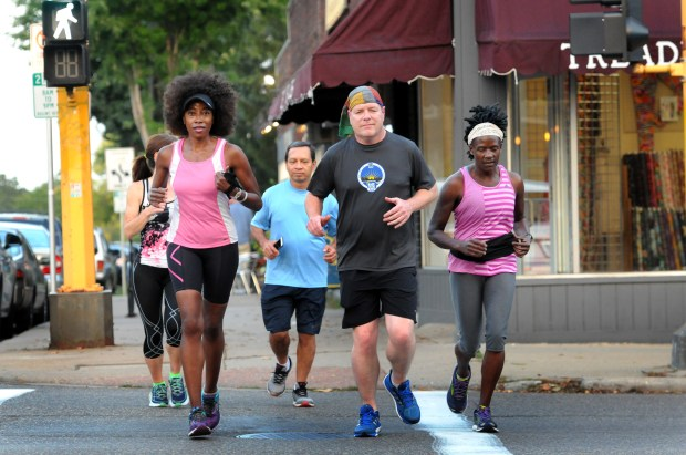 Yasmin Mullings, front left, joins her running instructor, Brandon D'Andrea, front right and others from her running group as they go on a training run in St. Paul on Thursday, Sept. 21, 2017. Mullings, a Ramsey County prosecutor, lost consciousness in a courtroom last year while grilling a key defendant in a complex, high profile sex-trafficking case. A month later she learned that a rare infection in her heart had caused the organ to fail and she had a heart transplant. Mullings ran a 10-mile race during Medtronic's Twin Cities marathon weekend on Oct. 1. Other runners in the back row, from left, are Jennifer Baldwin, Sandeep Kapil and Proscoria Ojamo. (Ginger Pinson / Pioneer Press)