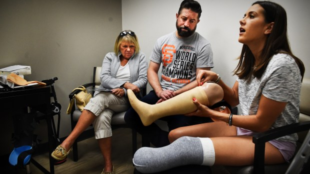 "Courtney Godfrey, right, sitting by her husband, Ryan Novaczyk and mother Barbara Godfrey, holds a sample prosthesis as she asks questions of Prosthetist Yakov ""Jacob"" Gradinar before he does casting for a temporary bent-knee prosthesis at Hanger Clinic in Minneapolis Friday, Sept. 29, 2017. Godfrey lost her lower leg following a boating accident Sept. 15. (Jean Pieri / Pioneer Press)"