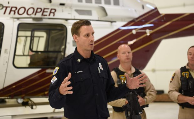 St. Paul Fire Department Capt. Steve Sampson speaks about the rescue of a lost hunter as, background, from left, Minnesota State Patrol pilot Jim Englin and Chief Pilot Lt. Craig Benz look on inside a hangar at St. Paul Downtown Airport Thursday, Sept. 21, 2017. (Dave Orrick / Pioneer Press)