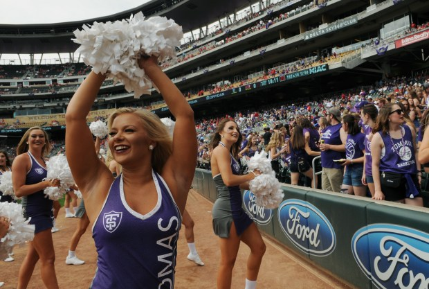 Krista Kronlokken, a St. Thomas Dance Team member, gets the fans warmed up as the University of St. Thomas takes on St. John's University at Target Field on Saturday, September 23, 2017 during a NCAA Division III matchup. St. Thomas won 20-17. (Pioneer Press / Ginger Pinson)