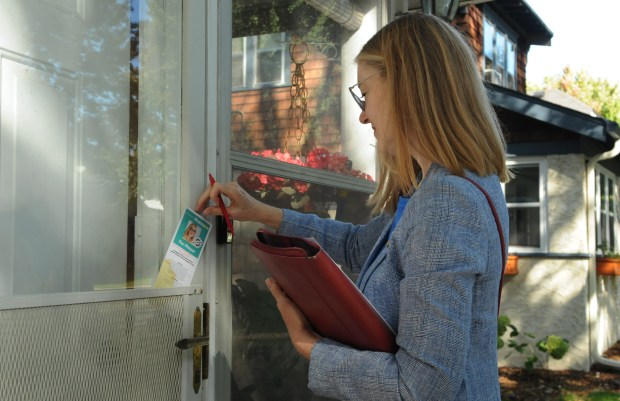 St. Paul mayoral candidate Elizabeth Dickinson leaves a campaign flyer on a door on Saratoga Street in St. Paul on Saturday, Sept. 30, 2017. (Ginger Pinson / Pioneer Press)