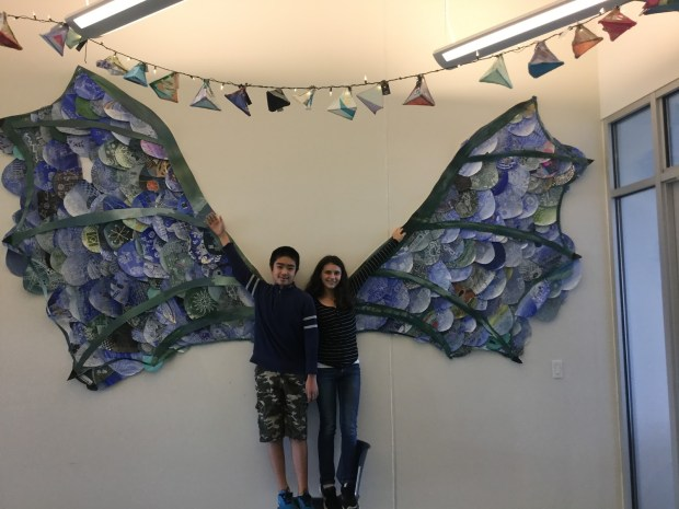Hailey and Baron pose with dragon wings at the Lakes International Language Academy in October 2017. They are posing to share they are bilingual.