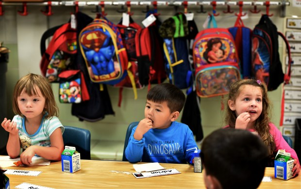 From left, Samantha Carlson, Adrian Vang, and Lydia Pettey have a snack at the start of class in Julie Heroff's preschool class at Castle Elementary School in Oakdale on Wednesday, Oct. 11, 2017. Heroff's class begins with a quick snack of Goldfish crackers and milk before students gather on a carpet in front of an interactive whiteboard. (Jean Pieri / Pioneer Press)