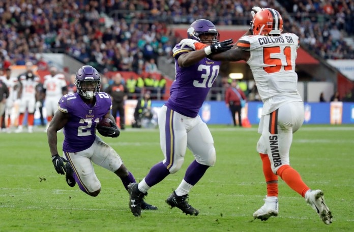 Minnesota Vikings running back Jerick McKinnon, left, scores on a 1-yard touchdown run as Vikings fullback C.J. Ham (30) holds back Cleveland Browns linebacker Jamie Collins Sr. (51) during the second half of an NFL football game against Cleveland Browns at Twickenham Stadium in London, Sunday Oct. 29, 2017. (AP Photo/Matt Dunham)