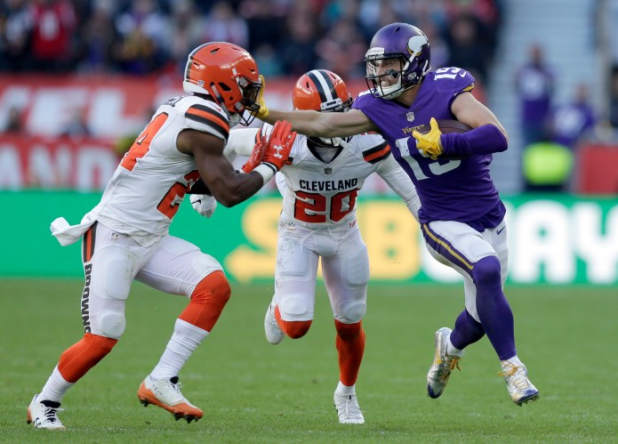 Minnesota Vikings wide receiver Adam Thielen, right, holds off Cleveland Browns' Ibraheim Campbell, left, and Briean Boddy-Calhoun (20) during the first half of an NFL football game at Twickenham Stadium in London, Sunday Oct. 29, 2017. (AP Photo/Tim Ireland)