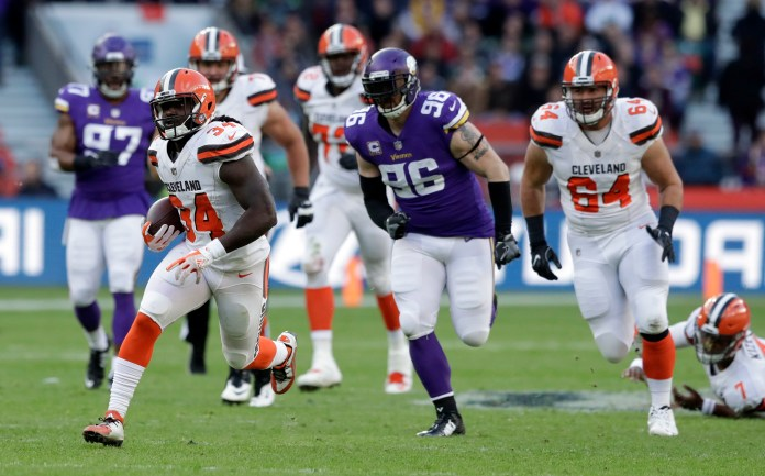 Cleveland Browns running back Isaiah Crowell (34) runs with the ball as Minnesota Vikings defensive end Brian Robison (96) and Browns center JC Tretter (64) watch during the first half of an NFL football game at Twickenham Stadium in London, Sunday Oct. 29, 2017. (AP Photo/Matt Dunham)