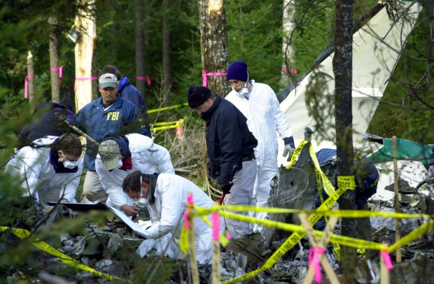 ** FILE ** Federal investigators sift through debris in this Oct. 27, 2002 file photo, from the twin engine plane that crashed two days earlier near Eveleth, Minn,. killing Sen. Paul Wellstone, his wife Sheila, daughter Marcia and several others. The National Transportation Safety Board is ready to vote on the likely cause of the 2002 accident. (AP Photo/Jim Mone, File)