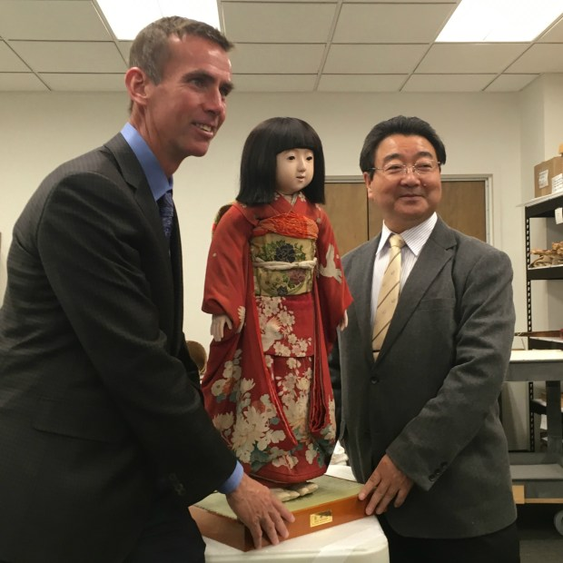 Alan Scott Pate, a U.S. expert on Japanese Friendship Dolls, and Masaru Aoki of the Yoshitoku Doll Company of Japan, pose with a newly restored Miss Miyazaki at the Minnesota Historical Society on Oct. 31, 2017. (Molly Guthrey / Pioneer Press)