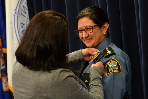 The commander's badge is pinned onto Pamela Barragan by her sister Erika, as a total of five in the St. Paul Police Department were promoted to Commander in a ceremony Monday at the St. Paul Police Western District Headquarters in St. Paul, Nov. 13, 2017. Barragan becomes the first Latina commander in the history of the St. Paul Police Department. (Scott Takushi / Pioneer Press)