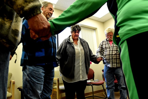 Vicki Burkhow, center, standing by Steve S., left, and Jim Hartman and others close a meeting with a 12-step prayer at Silver Sobriety in Stillwater, a non-residential recovery program that offers education, recovery services and support to adults ages 50 and older. (Jean Pieri / Pioneer Press)