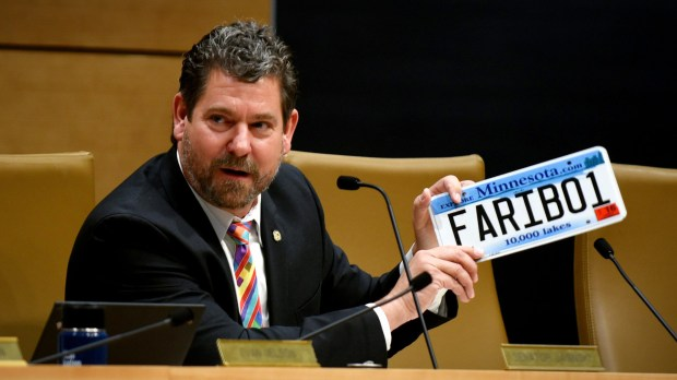 Minnesota state Sen. John Jasinski, R-Faribault, holds up his personal license plate during a hearing at the Minnesota Capitol on Wednesday, Nov. 15, 2017. Because of problems with a state computer system, such plates cannot be transferred from one vehicle to another right now. (Dave Orrick / Pioneer Press)