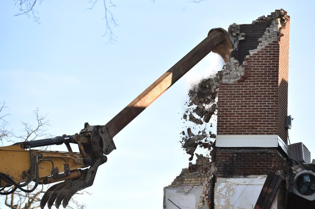 Construction crews use a excavator with a special arm to demolish the chimney at Minnehaha Academy in Minneapolis on Tuesday, Dec. 19, 2017. The school was severely damaged after a gas-line explosion on Aug. 2, 2017. (Pioneer Press / John Autey)