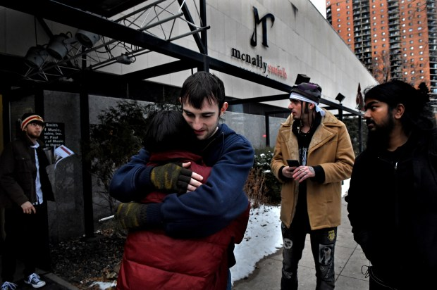 Alec Thicke, center, a production major at McNally Smith College of Music with one semester left of school, hugs Andie Fonseca, a production major that had two semesters left, outside the school on Dec. 15, 2017. The previous day it was announced the college would close. Second from right is Jozzy OG, (tan coat), a hip-hop major with one semester left who was about to start a piano performance major. (Jean Pieri / Pioneer Press)