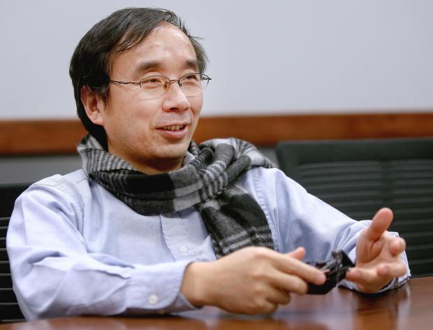 """Jeffrey Xu, an engineer who moved to Duluth from Shanghai to design a new airplane for Cirrus, describes how his dislike of the cold weather drove him to design his own easy-on, easy-off snowpants he calls """"Pants on Pants."""" (Bob King / rking@duluthnews.com)"""