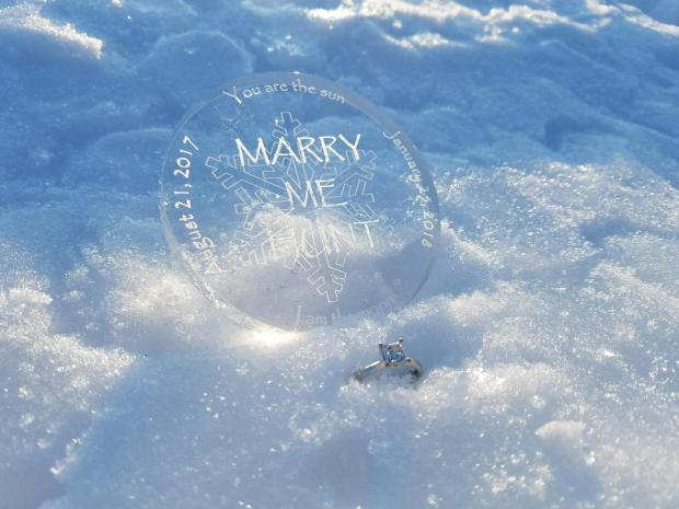 """Jana Armstead had this acrylic medallion made for her """"Marry Me Hunt"""" for Brad TeGantvoort, her longtime companion and fellow Treasure Hunter, after sending him out with clues to find his """"treasure"""" -- a flashmob of fellow Cooler Crew hunters, on Thursday, Jan. 25, 2017.. She propped the medallion in the snow along with hte enagement ring TeGantvoort gave her last summer. (Courtesy of Jana Armstead)"""