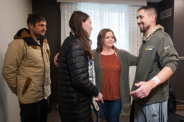 Erin Bond, center, 33, of Apple Valley, Minn., and her husband, John, right, 35, go in for a group hug with Olga Kemaeva, 34, the widow of Russian tourist Anton Kemaev, as they meet for the first time at the Residence Inn by Marriott on Thursday, Jan. 4, 2017, in Pittsburgh. At left is Kemaev's friend Vladimir Shlyakhtin. Mr. Bond believes he received Kemaev's kidney in a transplant operation he is currently recovering from. His family found out the donor was a 35-year-old Russian who had died from a gunshot wound and Googled the information, finding Kemaev's story in recent news. (Stephanie Strasburg/Pittsburgh Post-Gazette via AP)