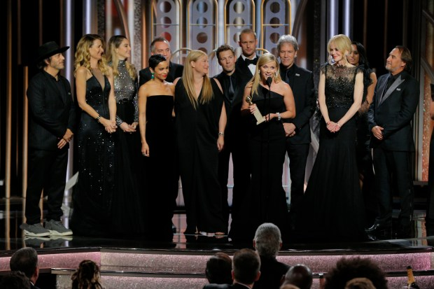 "This image released by NBC shows Reese Witherspoon, foreground, with the cast and crew of ""Big Little Lies,"" as she accepts the award for best limited series or motion picture made for TV at the 75th Annual Golden Globe Awards in Beverly Hills, Calif., on Sunday, Jan. 7, 2018. (Paul Drinkwater/NBC via AP)"