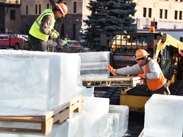 Chad O'Flanagan, left, and Taylor Dolan wth Park Construction Company muscle 650 pound blocks of ice off pallets at the site of the St. Paul Winter Carnival Ice Palace in Rice Park in St. Paul on Monday, Jan. 8, 2018. Flatbed trucks deliver 44 blocks at a time as the crews get ready to start building the Ice Palace starting Tuesday evening. (Pioneer Press / John Autey)
