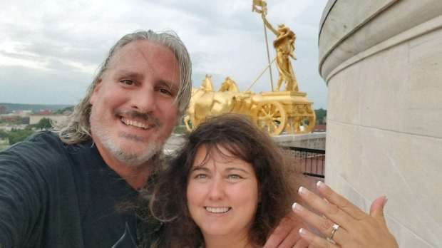 Jana Armstead, right, holds up her engagement ring from Brad TeGantvoort, left, near the Quadriga on a roof of the Minnesota Capitol on Aug. 21, 2017. TeGantvoort chose the day of the Great American Solar Eclipse to propose-- again -- an the two soon after got stuck on the terrace, locked out until the next tour arrived. (Courtesy of Jana Armstead)