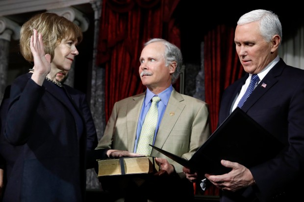Vice President Mike Pence, right, administers the Senate oath of office during a mock swearing in ceremony in the Old Senate Chamber to Sen. Tina Smith, D-Minn., left, with her husband Archie Smith, center, Wednesday, Jan. 3, 2018 on Capitol Hill in Washington. Sen. Smith will take over from Al Franken who resigned. (AP Photo/Jacquelyn Martin)