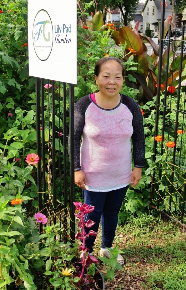 "Yer Vang stands in front of an arbor at Frogtown Green's ""Lily Pad"" garden in August 2017, a large community space at the corner of Dale Street and Lafond Avenue. (Photo by Hillel Natanson, courtesy of Patricia Ohmans)"