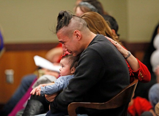 Savanna LaFontaine-Greywind's boyfriend Ashston Matheny holds their daughter, Haisley Jo, as victim impact statements are read during the sentencing of Brooke Crews at the Cass County District Court on Friday, Feb. 2, 2018. (David Samson / Forum News Service)