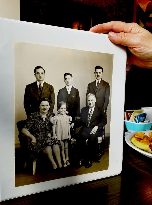 Marilyn Pitera, 81, holds a copy of a childhood family photo, showing her standing between her mother and father, Mary and Carl Pedro Sr., with siblings, from left, Carl Pedro Jr., Alfred Pedro and Eugene Pedro in the back row. In 2011, Pitera, Carl Pedro Jr. and Eugene Pedro gifted the city two vacant Pedro Luggage buildings and the land beneath them. The store, which closed in 2009, was torn down in 2011 at the request of the Pedro family, based on promises that the city would also remove its adjoining property and build parkland on par with downtown Rice Park or Mears Park. As of March 2018, no official parkland exists there, but city officials are hopeful a tentative development arrangement with the Ackerberg Group funds 20 years of parks improvements. Pitera, the last living land donor, has objected to the deal. (Courtesyo of Marilyn Pitera)