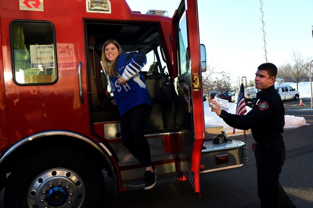 Hannah Brandt, left, arrives on a Vadnais Heights fire truck at a welcome home celebration in Vadnais Heights on Thursday, March 8, 2018. Her sister, Marissa, was on another fire truck. The Olympian sisters represented two different countries, with Marissa competing with the Korean Women's Hockey Team and Hannah on the U.S. Women's Hockey Team at the PyeoneChang 2018 Olympic games. (Jean Pieri / Pioneer Press)