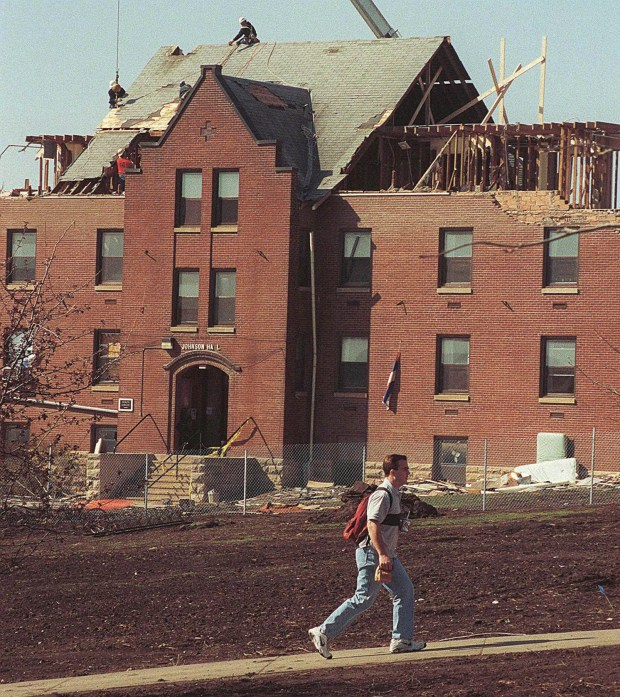 A Gustavus Adolphus College students heads back to school Tuesday April 21, 1998 as workers repairing Johnson Hall, in St. Peter, Minn. It was the first day of school for the college since it received more than $60 million in damages from a March 29 tornado. (AP Photo/Mankato Free Press, Brett Groehler)
