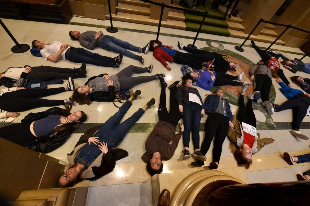 Twenty-two people lie on the floor outside the Minnesota House of Representatives to call for stricter gun control laws during a demonstration at the State Capitol in St. Paul on Thursday, March 22, 2018. (Dave Orrick / Pioneer Press)