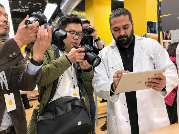 An instructor at Lane Tech College Prep, an inner-city Chicago magnet school, uses a new iPad with Pencil-stylus support as the tech media look on. Apple held a press event on Tuesday, March 27, 2018, at the high school, which was a staging area for a barrage of education announcements as Apple aims to stay competitive in the classroom market. (Julio Ojeda-Zapata / Pioneer Press)