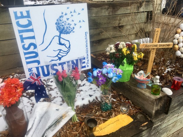 A memorial to Australian Justine Ruszczyk Damond is displayed Wednesday, March 21, 2018, near the alley where a Minneapolis police officer shot and killed her in July 2017 in Minneapolis. Neighbors, friends and activists held a vigil for Damond after the officer was charged in her death. (AP Photo/Jeff Baenen)