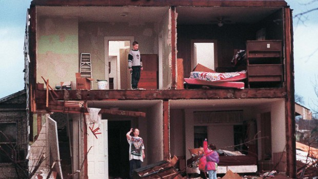 Residents of a storm-damaged home along North Seventh Street in St. Peter, Minn., survey damage to their home after a tornado ripped through the town Sunday, March 29, 1998.(AP Photo/Mankato Free Press, Greg Abbott)