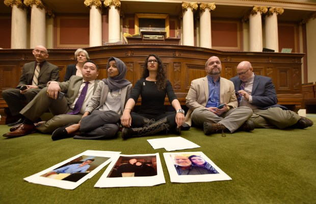 Rep. Erin Maye Quade, DFL-Apple Valley, center, sits with other lawmakers amid photos of local people shot in crimes in the chamber of the Minnesota House of Representatives on Tuesday, April 24, 2018. Maye Quade was planning to remain there for 24 hours telling stories of victims of gun violence. Depicted in the photos are, from left: Chase Passauer, shot and killed in a St. Paul law office in 2016; Shelley Joseph-Kordell, shot and killed in the Hennepin County Government Center in 2003; Rick Hendrickson, survived being shot in the neck at close range during the same 2003 Hennepin County Government Center shooting. (Dave Orrick / Pioneer Press)