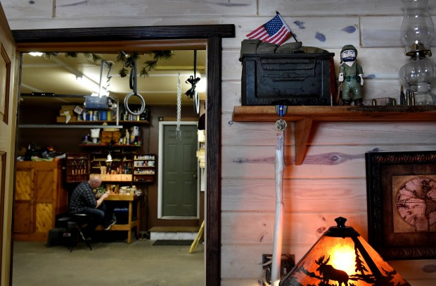 In his garage office, on a shelf at top, right, Tanner Spicer has a tribute to his grandfather, a Korean War-era soldier. (Jean Pieri / Pioneer Press)
