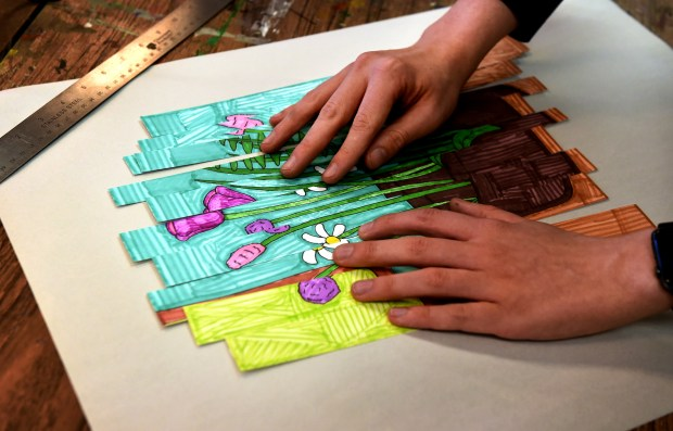 After he finishes drawing a picture of flowers, Devin Wildes, slices it and rearranges it before gluing it to paper at Interact Center for Visual and Performing Arts, Thursday, April 19, 2018. (Jean Pieri / Pioneer Press)